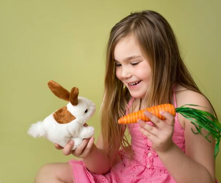 Happy smiling girl feeding a carrot to the Easter Bunny