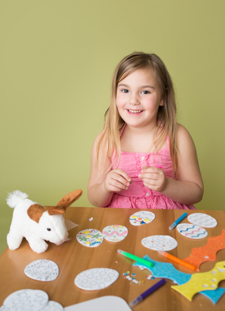 Happy smiling child doing Easter activities and crafts with bunny stickers, Easter Egg shapes, pencils and markers.