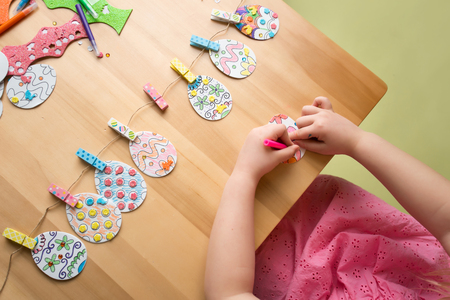 creativity: Child doing Easter activities and crafts with bunny stickers, Easter Egg shapes, pencils and markers.