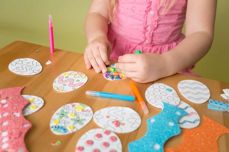 niños jugando: Niño que hace actividades de Semana Santa y artesanías con pegatinas de conejo, formas del huevo de Pascua, lápices y marcadores.