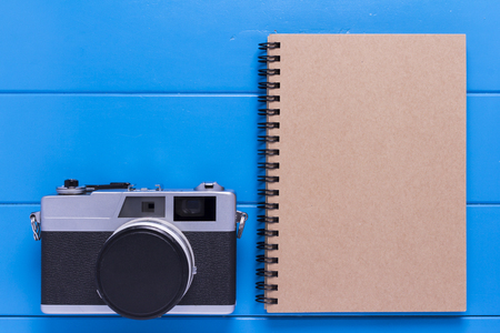 Vintage camera and note book paper on blue wood background. Reklamní fotografie