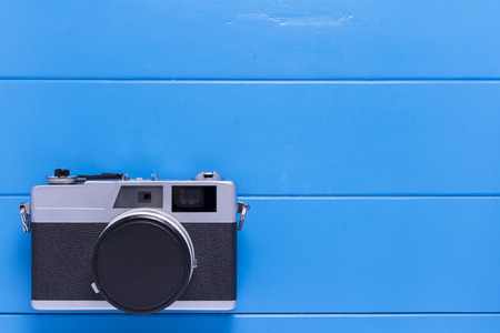 Vintage camera on blue wood background with Copy Space for Text.