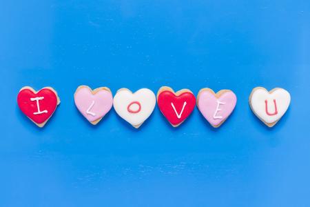 i love you heart: I Love You - Heart shaped cookies on blue wood background.