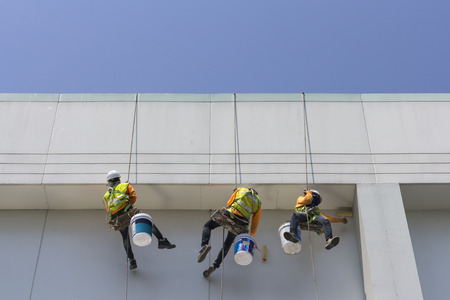 Painters and harnesses hanging high building