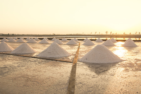 Heap of sea salt in salt farm during sunset in Thailand.