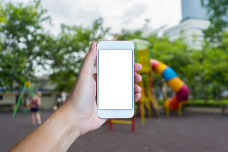 walk path: Mans hand shows mobile smartphone with white screen in vertical position,  outdoor play park  blurred background - mockup template and clipping path Stock Photo