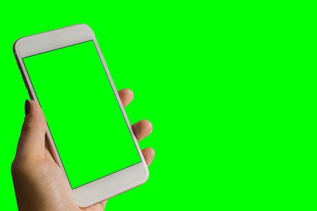woman's hand shows mobile smartphone with green screen in vertical position isolated on green background - mockup template and clipping path 写真素材