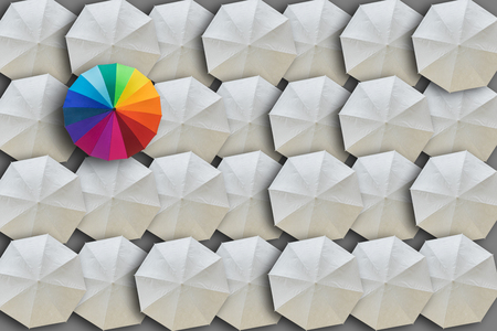 Concept of Leadership, Different and Distinction.Colorful umbrella and many white umbrellas around Stock Photo