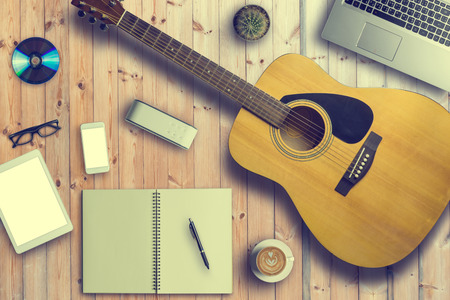 Concept of Music Musician and Song Writer. Guitar, CD, Cactus, Laptop, Glasses, Tablet, Smartphone, Bluetooth Speaker, Cup of Latte or Cappuccino Coffee, notebook and pen on wooden table.Copy Space Фото со стока