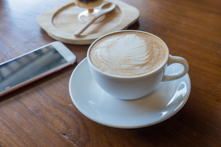 Cup of hot coffee ad smartphone put on old wooden table background.Copy space Stock Photo