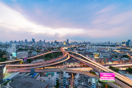 Sunset scene of Bangkok cityscape with blue sky and clouds. Traffic on the freeway in the business district. at dusk.Expressway and Highway top view.Twilight scene with traffic light Thailand. Stock Photo