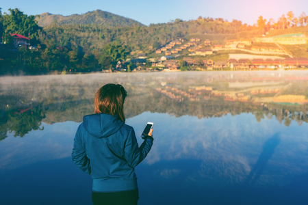 Beautiful asian woman used smartphone and making selfie outdoors with Sunrise scence of Ban Rak thai village in Mae Hong Son veiw of mountains under mist near Chiang Mai, Thailand with vintage tone