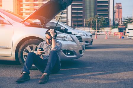 젊은 아시아 잘 생긴 남자가 깨진 아래로 차로 앉아 스마트 휴대 전화를 사용하여 도움을