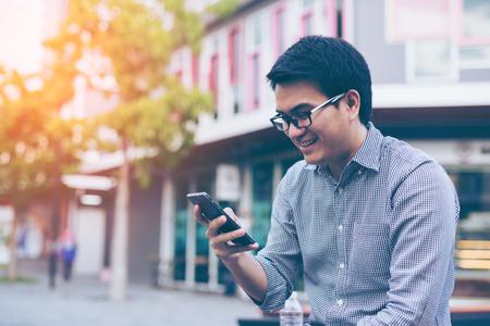 그의 스마트 폰을 읽는 동안 웃는 젊은 아시아 잘 생긴 사업가. 스마트 전화 야외에서 메시지를 읽고 아시아 비즈니스 사람 (남자)의 초상화. 스톡 콘텐츠