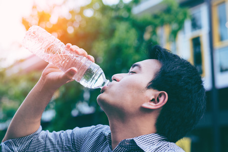 Handsome asian businessman in casual cloth drinking water from a bottle in park