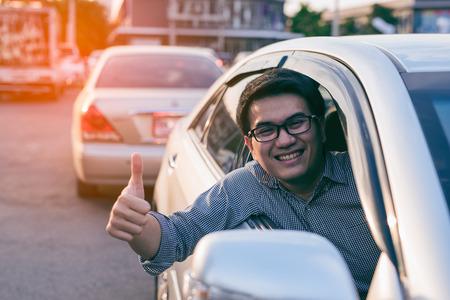 Junger asiatischer gutaussehender Mann, der Daumen in seinem Auto lächelt und zeigt