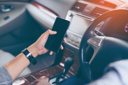 Hand's man using smartphone while driving the car (selective focus) - transportation and vehicle concept Standard-Bild