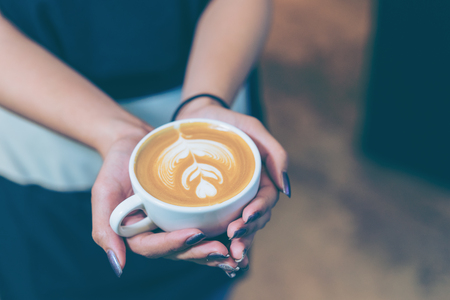 Women hands holding fresh coffee or latte art in white cup at coffee shop and restaurant, bar or pub.
