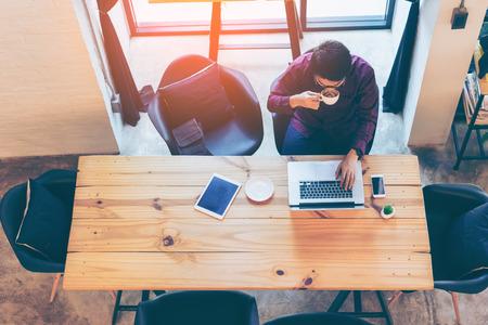 Topview 자신의 노트북을 사용 하 고 커피 카페에서 커피를 마시는 동안 웃 고 젊은 아시아 잘 생긴 사업가. 커피가 게에서 랩톱을 사용하는 아시아 비즈