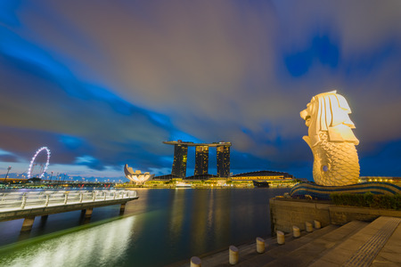 AUGUST 18, 2016 SINGAPORE : The Merlion is a traditional creature with a lion head and a body of a fish, seen as a symbol of Singapore.Landscape of the Singapore landmark financial district at sunrise