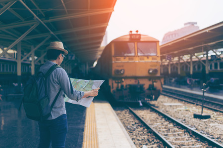 Young man traveler with sky blue backpack and hat looking the map with train background at train station Bangkok. Traveling in Bangkok Thailand. Travel concept Standard-Bild