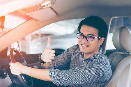 Молодой азиатский красивый человек улыбается и показывает палец вверх в своем автомобиле