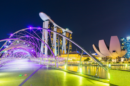Helix Bridge travel landmark and Marina Bay Sands Resort Hotel at night scene with black sky and clouds in Singapore Фото со стока