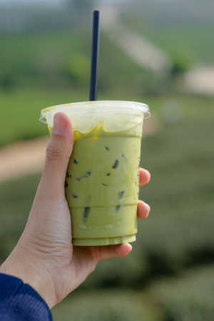 Mans hand holding a cup of cold japanese matcha green tea with milk. tea farm background