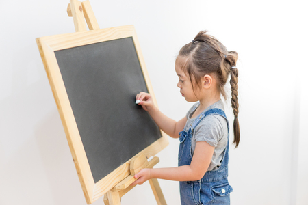 Little girl draws chalk on blackboard with happiness in home