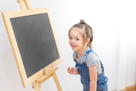 Little girl draws chalk on blackboard with happiness