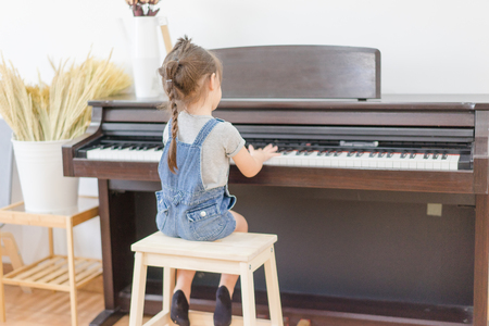 Cute little girl playing piano in  bedroom.