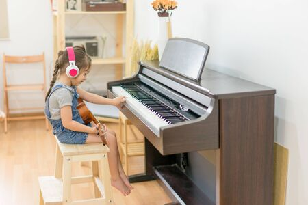 Cute little girl with headphone playing piano and ukulele in  bedroom with happiness