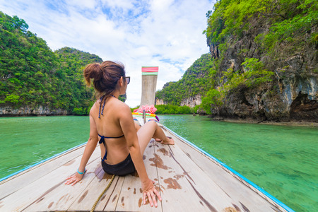 Traveler Summer concept - Beautiful woman in bikini traveling on long boat to Hong Islands in andaman sea Krabi, South of Thailand.
