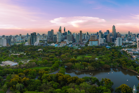 Sunset scence of Bangkok skyline Panorama ,Aerial view of Bangkok modern office buildings and condominium in Bangkok city downtown with sunset sky and clouds at Bangkok , Thailand. Lumpini park Фото со стока