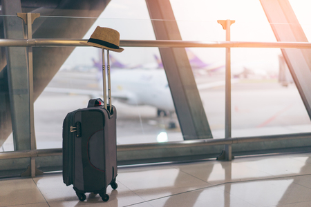 Suitcase and hat in international airport departure lounge, airplane in background, traveler concept, traveler baggage and hat in airport terminal waiting area, focus on luggage