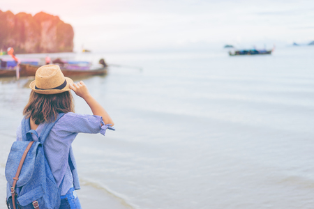 Young woman traveler with sky blue backpack and hat looking the sea with long boat thailand background from Ao Nang Beach Krabi. Traveling in Krabi Thailand , Traveler summer concept