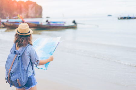 Young woman traveler with sky blue backpack and hat looking map at the sea with long boat thailand background from Ao Nang Beach Krabi. Traveling in Krabi Thailand , Traveler summer concept