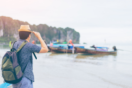Young man traveler with green backpack and hat looking at the sea with long boat thailand background from Ao Nang Beach Krabi. Traveling in Krabi Thailand , Traveler summer concept Фото со стока