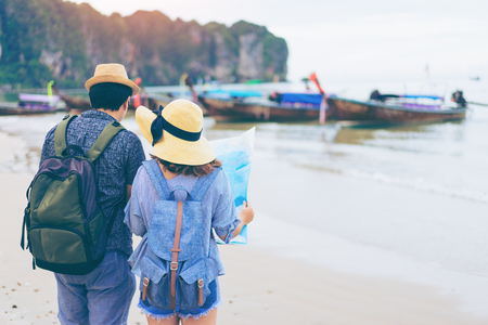Young love couple traveler with backpack and hat looking map at the sea with long boat thailand background from Ao Nang Beach Krabi. Traveling in Krabi Thailand , Traveler summer concept