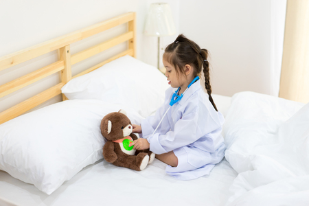 Little girl play a toy scope and doctor with a doll on the bed , kid concept , children and healthcare , Learning concept