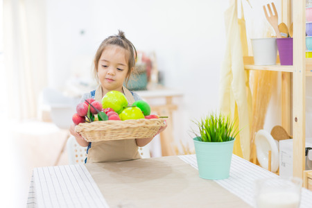 Beautiful little girl looking fruits  in basket on kitchen table at house