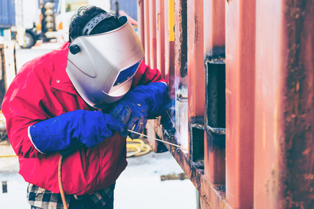 Welder worker repair the damage container wall, Industrial at the factory welding.  Worker repair container box by gas cutting and welding heavy job. worker while doing a welding with arc welder Фото со стока