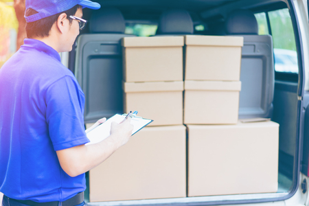 Delivery concept - Smiling happy young asian handsome male postal delivery courier man in front of cargo van delivering package checking carton with service mind and blue uniform