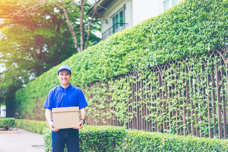 Delivery concept - Smiling happy young asian handsome male postal delivery courier man in front of house delivering package carrying box with service mind and blue uniform Фото со стока