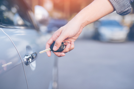 Mens hand using key unlock doors car
