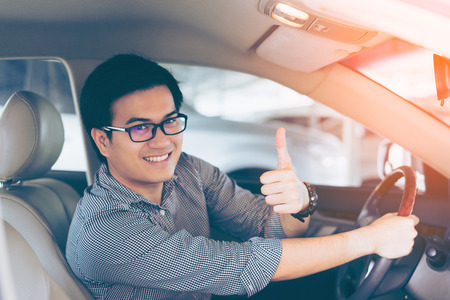 Portrait of asian happy handsome man showing thumbs up while driving car