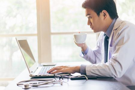 Ritratto di un giovane medico bello utilizzando il suo computer portatile e bere caffè con un volto serio