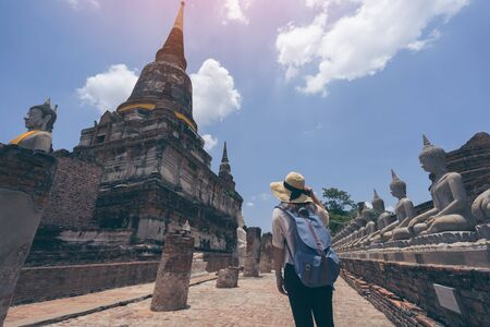 Young woman traveler with sky blue backpack and hat looking Wat Yai Chai Mongkol (or Mongkhon) temple background from Ayutthaya near Bangkok Thailand. Traveling in Ayutthaya near Bangkok Thailand 版權商用圖片