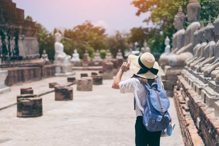 젊은 여자 여행자 하늘 파란색 배낭과 모자 와트 핫 야이 차이 티 Mongkol (또는 Mongkhon) 사원 백그라운드에서 방콕 태국 근처 아유타야에서 찾고. 태국 방 스톡 콘텐츠