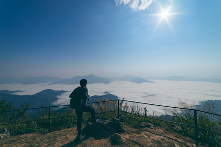 Man tourist is traveling into the peak of mountain and cloudscape at Doi Pha Tang in Chiangrai Thailand. Man traveler with bag standing looking beautiful mist at sunrise. Hiking trekking concept